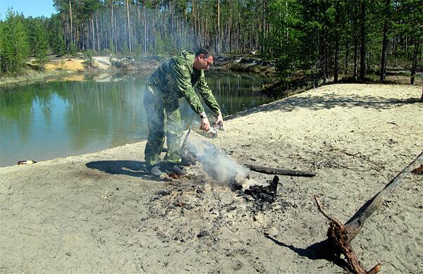 Желательно совмещать все методы тушения костра - полить его водой, присыпать землей и разбросать угли.