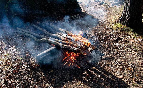 При таком расположении дров прогорающие части падают в костер и продолжают тлеть, а их тепло отражается от большого бревна и греет человека.