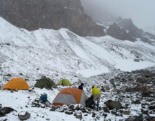 В таком биваке необходимо сделать стенку из камней вокруг палаток и предусмотреть защиту для горелок от ветра.
